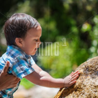 Mother supporting her toddler boy as he explores touching a natural water fountain outdoors and splashing