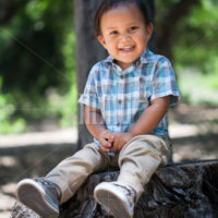 Cute mexican boy with plaid shirt and great healthy smile with baby teeth sitting outdoors during summer in california national park