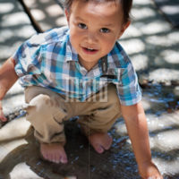 2 year old boy crouching down and touching a water fountain with his hand, getting wet and having fun in summer