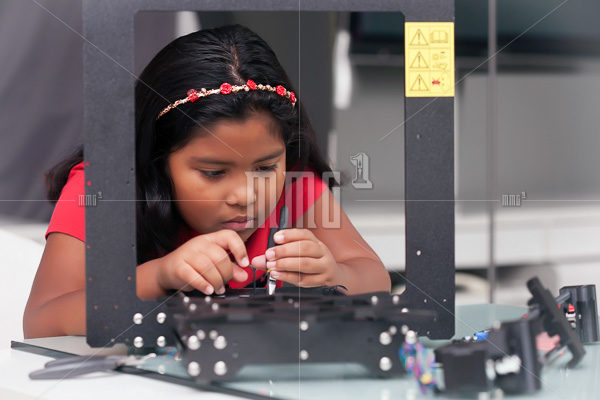 Young girl, 8 year old assembling a 3D printer kit for STEM summer camp