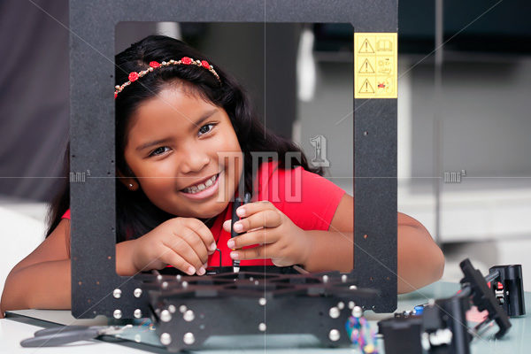 Happy 8 year old girl building a 3D printer kit for summer engineering camp or class