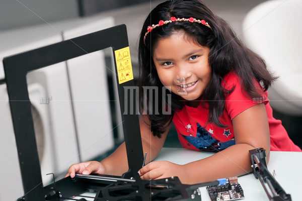 Little girl learning and working hands on, building a 3D printer with assembled pieces on desk