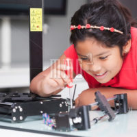 Genius level kid learning about 3D printers by building it and following directions in STEM class
