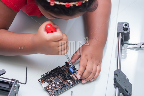 Little hands of a smart kid working on electronic device with a screw driver on hand and other components for summer camp