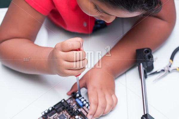 Young child learning about electronics and technology by wiring and holding screw driver making a connection in class