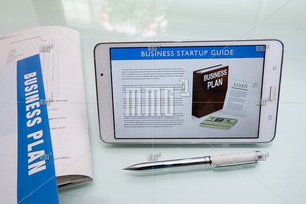 Writing a business plan using a business startup guide, printed collateral, pen, and tablet or mobile device on a reflective glass desk.