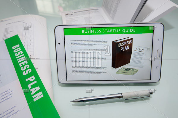 Business startup guide on tablet or mobile phone with business plan documents and fancy pen for writing.