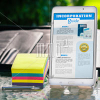 Entrepreneurial business research and planning which includes a mobile phone, tablet, notes, pen and professional binder in an outdoor setting.
