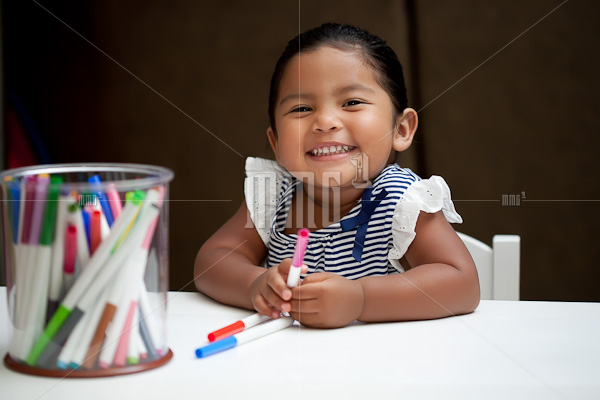 Little girl smiling and holding markers on white table