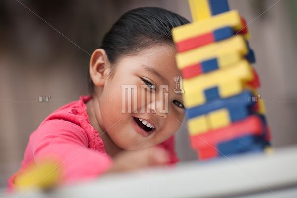 Hispanic girl looking happy and playing with colorful building blocks